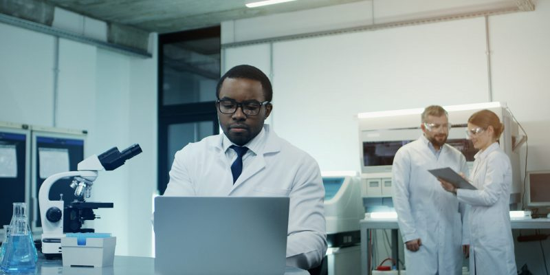 African American young man scientist in the white robe and glasses working at the laptop and microscope over research while his female caucasian co-worker coming with a tablet