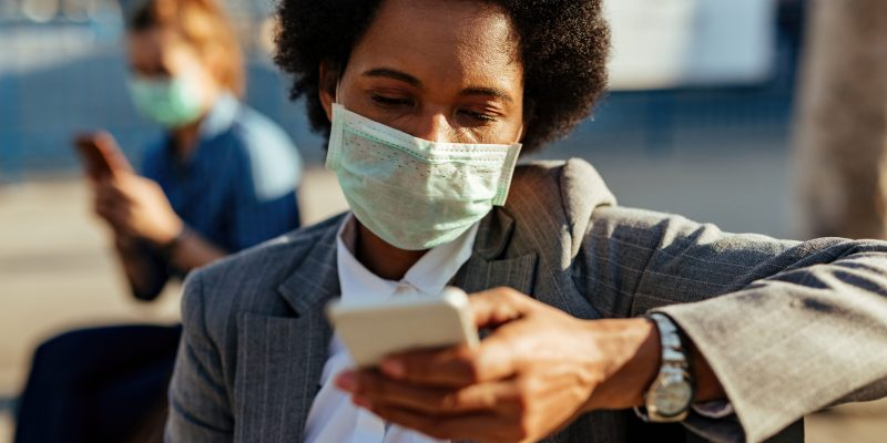African American businesswoman wearing face mask and texting on cell phone on the street.