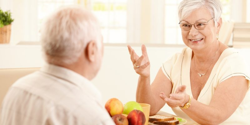 Elderly wife chatting to husband at breakfast