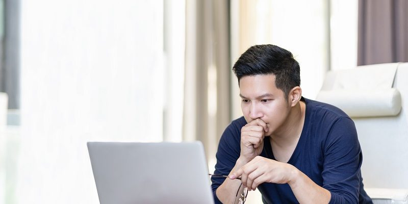 seriously confident asian young freelancer in smart casual working and concentrated on laptop sitting on desk in modern office ,co-working space or at home with copy space, webinar over the internet